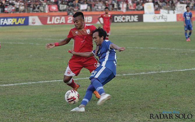 Bek Persis Solo Dedi Tri Maulana (kiri) melawan penggawa PSIM Ichsan Pratama di laga terakhir babak penyisihan grup timur Liga 2 2019