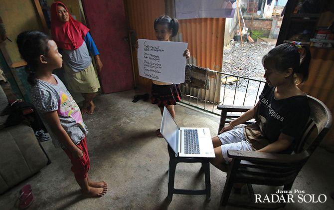 LEBIH RILEKS: Seorang siswa sedang mengerjakan soal ujian sekolah dari rumah dengan pengawasan orang tua, kemarin (23/3).