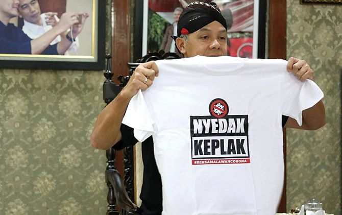 Gubernur Jateng Ganjar Pranowo menunjukkan salah satu kaos gaul bertema pencegahan Covid-19.
