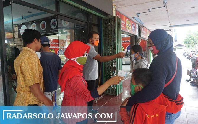 Karyawan mengukur suku tubuh pengunjung yang hendak masuk Plasa Klaten, kemarin (21/5). Sejumlah pusat perbelanjaan terpantau padat.
