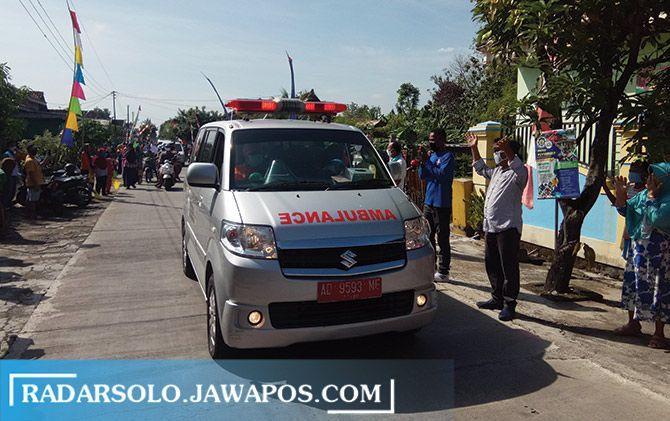 Ambulans yang membawa bidan Suwarti pulang ke rumah, disambut warga dengan antusias.