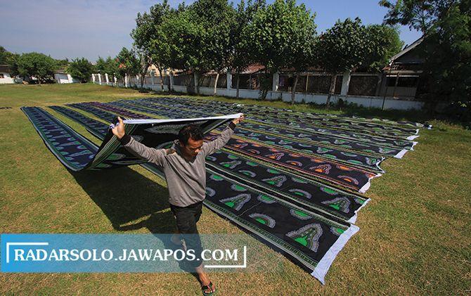 TERIK: Pekerja menjermur kain batik di Lapangan Sriwaru, Sondakan, Laweyan, kemarin (4/7). Lokasi ini digadang-gadang menjadi lapangan pendukung Stadion Manahan dalam event Piala Dunia U-20 tahun depan.