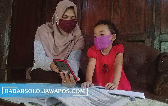 Ilustrasi orang tua mendampingi anak saat belajar daring.