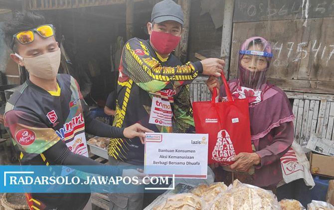 Peserta Alfamart Gowes Sabang sampai Merauke membagikan paket sembako kepada warga.