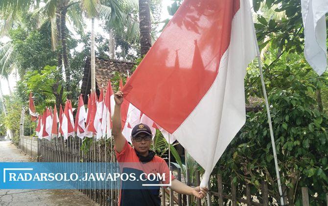 Asim menunjukkan puluhan bendera merah putih yang dipasang di depan rumahnya di Desa Krakitan, Kecamatan Bayat, Klaten.