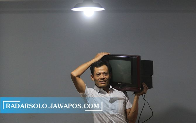 BIKIN BANGGA: Kusrin menggotong televisi tabung hasil produksinya di Wonosari, Jatikuwung, Gondangrejo, Karanganyar.