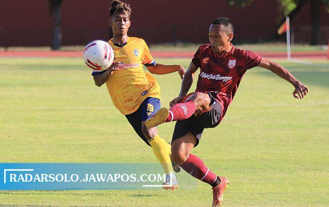 Bek Persis Solo Anis Mujiono membuang bola, dan hendak direbut pemain Persika Karanganyar saat uji coba di Stadion UNS, Rabu (7/10).