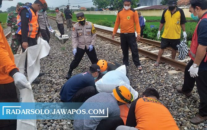 Polisi mengevakuasi jasad pengendara motor yang tewas usai tertabrak kereta api di Kaponan, Desa Jetak, Kecamatan Sidoharjo, kemarin (18/12).