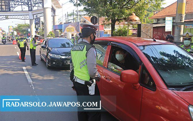 Petugas memeriksa kendaraan yang menggunakan pelat luar Kota Solo di Tugu Makutho tahun lalu.