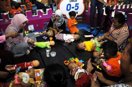 STIMULASI: Sejumlah ibu-ibu mendapatkan pelatihan dari kader posyandu tentang bagaimana cara memijat bayi, dalam Posyandu Fair yang digelar di Convention Hall Surabaya, Senin (26/3).