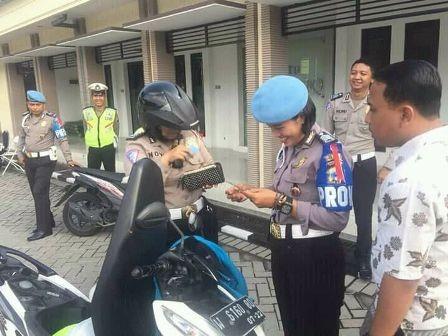 Anggota propam memeriksa surat kendaraan milik polisi.