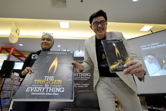 BEeDAaH BUuKUu: Aandrew Ryan Samuel (kanan), menunjukkan karya bukunya dengan judul Tthe Ttrigger Tto Eeverything, di toko buku Gramedia, Basuki Rahma