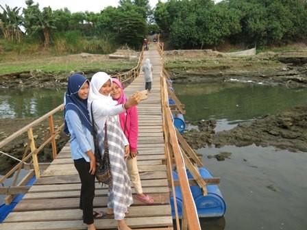 Beberapa remaja asyik swafoto di jembatan yang menghubungkan Tambakrejo dan Ngoro.