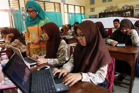 BENTUK APRESIASI: Seorang guru sedang mengajar murid-muridnya di SMAN 5 Surabaya.