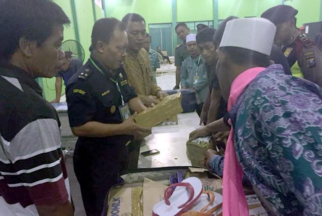DIPERIKSA: Petugas Bea Cukai menyita rokok yang dibawa oleh para CJH yang melebihi ketentuan di Asrama Haji Sukolilo.