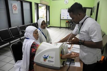 TES KESEHATAN: Petugas kesehatan di klinik Asrama Haji Embarkasi Surabaya (AHES), memeriksa tekanan darah Umi Kulsum, CJH kloter 33 asal Kota Blitar, Jumat (27/7).