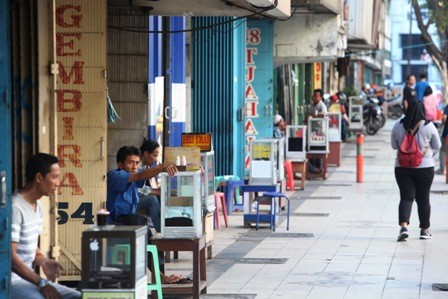 TUNGGU PENJUAL EMAS: Para pedagang kaki lima yang berjualan di depan toko emas di Pasar Baluran Jalan Bubutan.