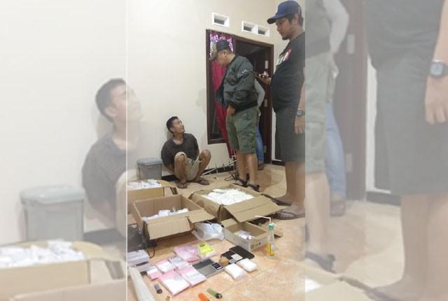 Tertangkap : Suhendrik Setiawan (duduk) tengah ditanya petugas BNNP Jatim
