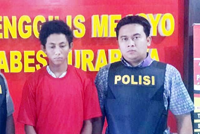 DITAHAN: Tersangka Edi Santoso diapit Tim Anti Bandit Polsek Tenggilis Mejoyo.