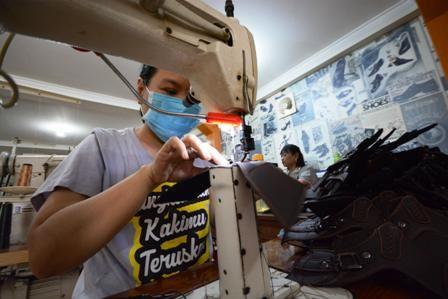 BUTUH DORONGAN: Pekerja sedang membuat sepatu dan sandal di kawasan Dolly, Surabaya. Hingga kuartal ketiga 2018, pertumbuhan industri sepatu domestik di Jatim turun sebesar 20 persen.