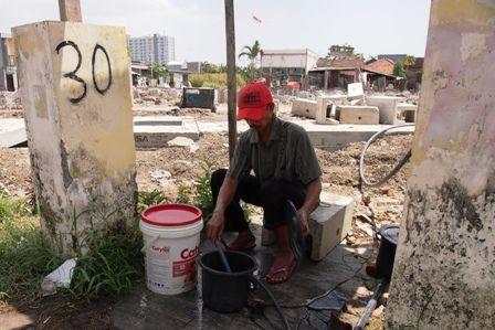 CARI  AIR: Roji, salah satu warga Gunungnanyar Lor, mengambil  air yang terbuang dari bocornya pipa PDAM akibat terkena dampak proyek Merr,  untuk memenuhi kebutuhan air bersih.
