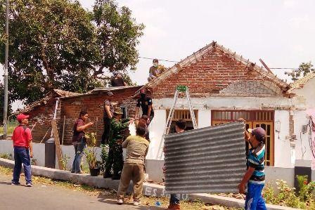 GOTONG ROYONG: Warga bersama TNI/Polri membantu memperbaiki atap rumah warga di Desa Kajeksan, Tulangan, yang dilanda angin puting beliung.