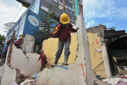 DIBONGKAR: Dengan menggunakan alat berat dan tenaga manusia, bangunan yang terimbas rencana pelebaran Jalan Wonokromo, Surabaya dan sudah dilakukan pe