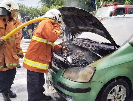 PEMBASAHAN: Petugas pemadam kebakaran melakukan pembasahan terhadap mesin mobil yang terbakar.