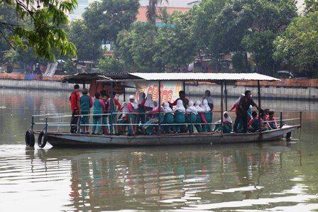 MASIH DIMINATI: Para pengguna fasilitas layanan penyeberangan sungai di kawasan Wonokromo, Surabaya.