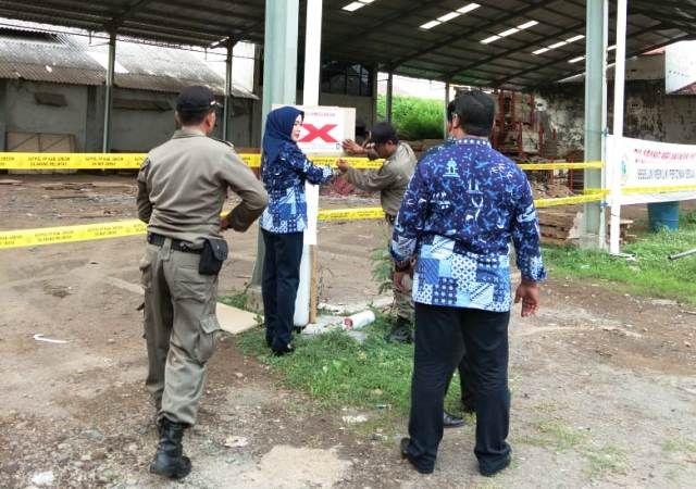 DISEGEL: Satpol PP bersama DPM-PTSP melakukan penyegelan terhadap PT SSM di Balongpanggang.