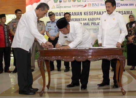 TERINTEGRASI: Bupati Saifu Ilah (tengah) didampingi Wabup Nur Ahmad Syaifuddin (kanan) dan Sekda Achmad Zaini menandatangani MOU Mal Pelayanan Publik
