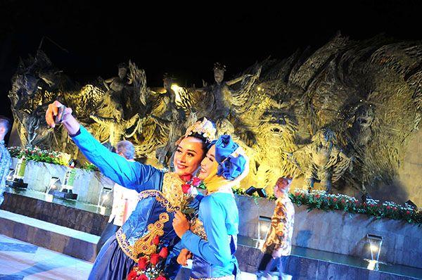 SWA FOTO: Dua orang penari berswa foto dengan latar belakang Tugu Parasamya Purnakarya Nugraha, yang telah diresmikan oleh Gubernur Jatim, Soekarwo, d