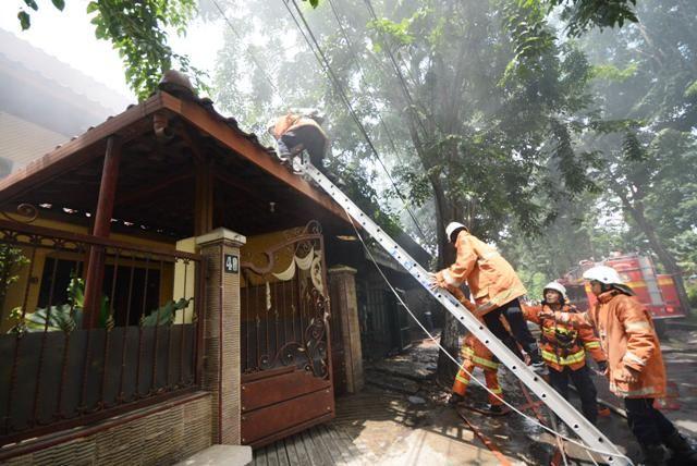 LUDES: Petugas berusaha memadamkan api saat kebakaran melanda sebuah bengkel di Surabaya, Rabu (2/1).