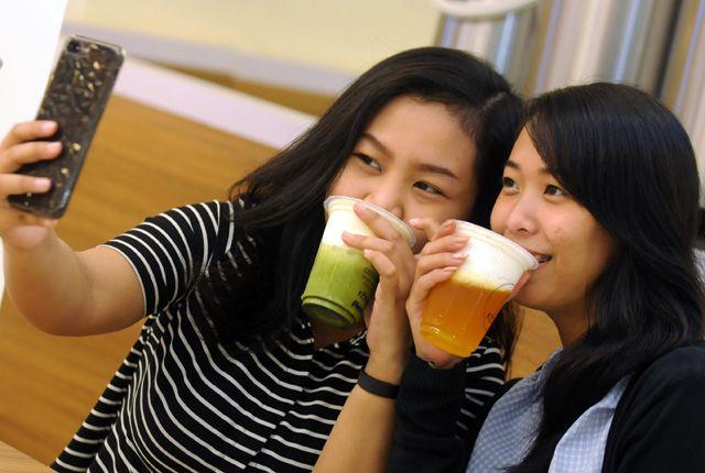 SEDANG BOOMING: Nisa (kiri) dan Natalia berswafoto saat menikmati minuman kekinian cheese tea, di Royal Plaza Surabaya, Rabu (9/1).