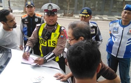 KOMPAK: Petugas melakukan penilangan terhadap salah seorang pengendara yang terjaring operasi gabungan.