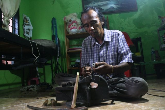 TELATEN: Perajin Keris, Ainul Yahya sedang menyelesaikan pembuatan keris di rumahnya.