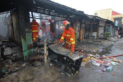 LUDES: Petugas pemadam kebakaran melakukan pembasahan saat kebakaran melanda kios di Jalan Teluk Nibung, Perak Utara.