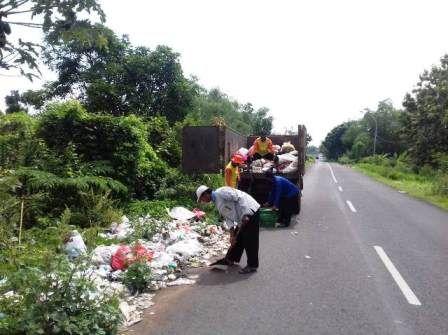 BERSIH-BERSIH : Petugas DLH Gresik saat membersihkan sampah yang ada di pinggir jalan.