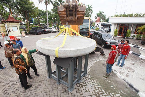 SIAP DIGELAR: Petugas menggunakan alat berat mengangkat cobek berukuran besar yang akan digunakan pada Festival Rujak Uleg di Tugu Pahlawan, Surabaya,