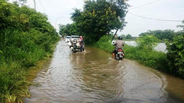 TERGENANG: Pengendara motor harus berhati-hati saat melintas Jalan Raya Ganggang, Kecamatan Balongpanggang agar tidak mogok.