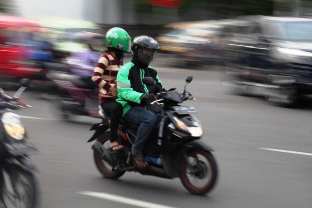 ADA ATURANNYA: Driver ojek online membawa penumpang melintasi jalan protokol Surabaya