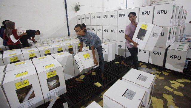 BURU WAKTU: Pekerja menyortir dan menyegel kotak suara beserta surat suara Pemilu 2019 di kawasan Kalilom, Surabaya.