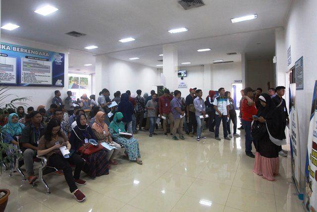 DISERBU: Warga antre untuk melakukan perekaman saat mengurus Surat Ijin Mengemudi (SIM) di Satpas Colombo, Surabaya, Senin (22/4).