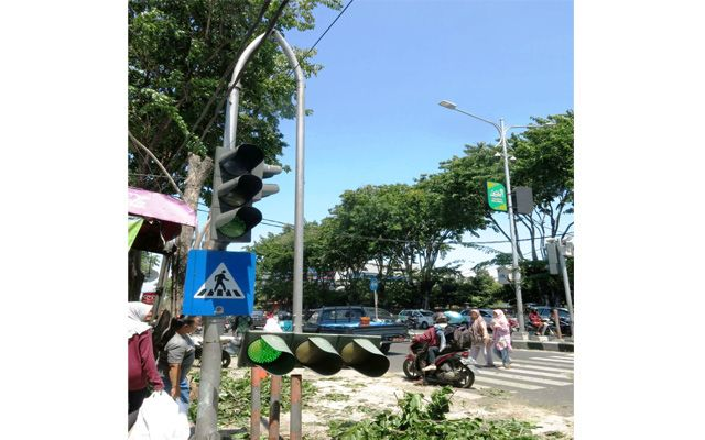 MELENGKUNG: Tiang TL di Jalan Mojopahit yang patah dan menjuntai ke bawah.