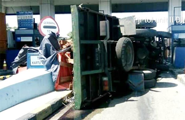 TERGULING: Kondisi truk tronton pasca menabrak mobil lain dan akhirnya berhenti setelah menabrak pintu gerbang tol Tandes Barat.
