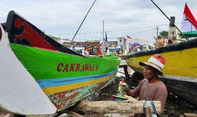 NGECAT BARENG: Sejumlah nelayan saat melakukan pengecatan perahu menyambut ramadan pekan depan.