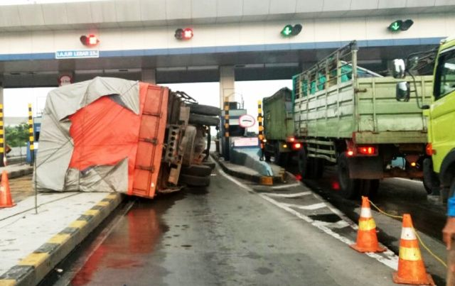 TAK TERKENDALI: Diduga rem blong truk muatan karton terguling di pintu tol Tandes Barat.