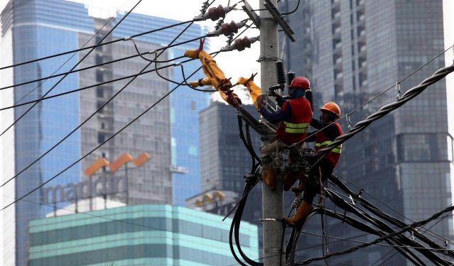ANTISIPASI: Pekerja menyelesaikan perbaikan jaringan listrik PLN di kawasan Jalan Gubernur Suryo, Surabaya.