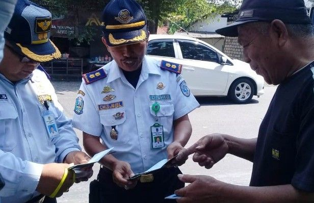 TIDAK LENGKAP: Petugas LLAJ Dishub Gresik melakukan razia angkutan di Jalan Raya Driyorejo.