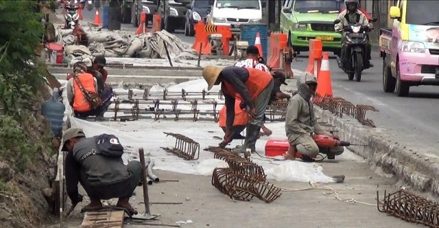 DIKEBUT: Para pekerja saat melakukan perbaikan jalan di kawasan ruas Surabaya-Gresik di kawasan Romokalisari, Surabaya.